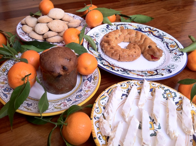 Four seasonal desserts: a tiny panatone, a plate of almond cookies, a eel shaped almond flavored torciglione and slices of almond torrone