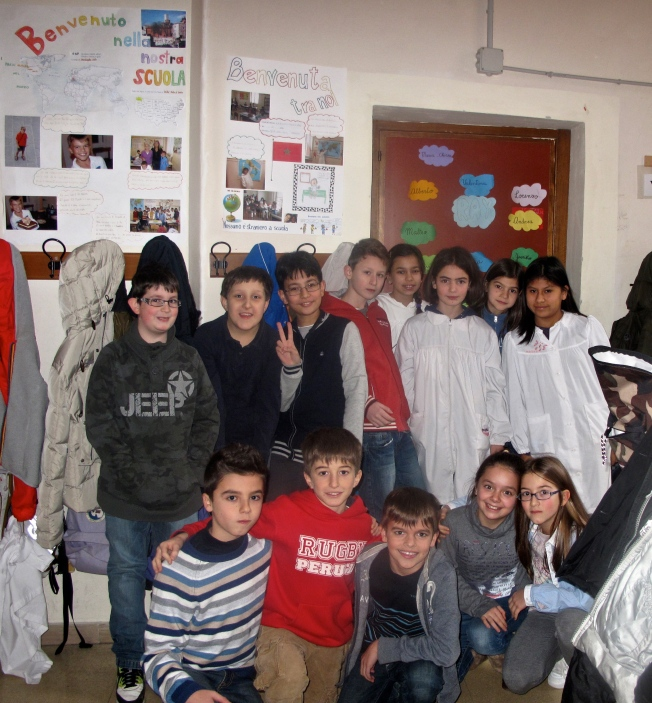 "This is me with my classmates.  I'm sitting between Andrea and Gaia.  In the background is poster of me that my class made at the beginning of the year.  It says, ""Welcome to our school."""