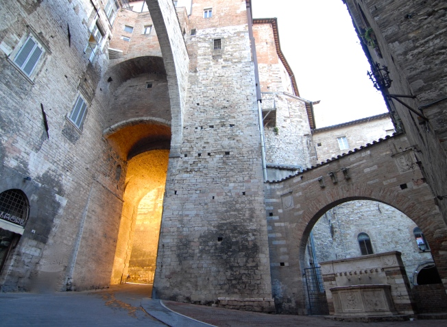 Sunrise filling the archway to Piazza IV Novembre.