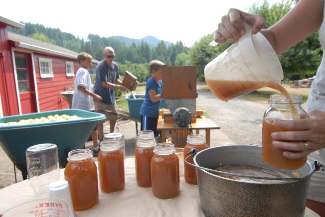 Heidi fills jars after the guys press the fruit.